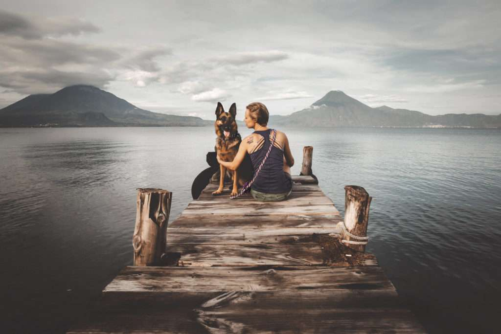 German Shepherd dog and blond woman sit on wooden dock over lake with tall volcanoes and clouds