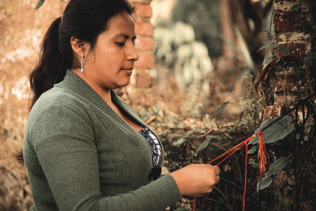 Woman artisan ties macrame ribbon in natural setting