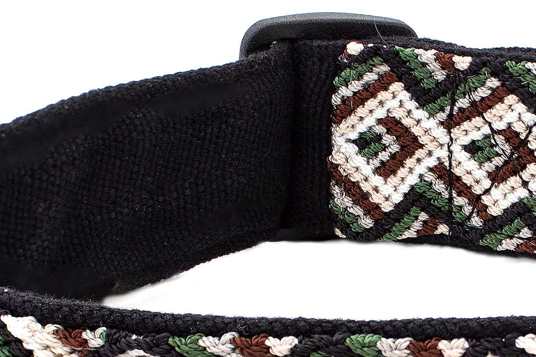 Closeup of black richly textured handwoven fabric backing on brown and green dog collar