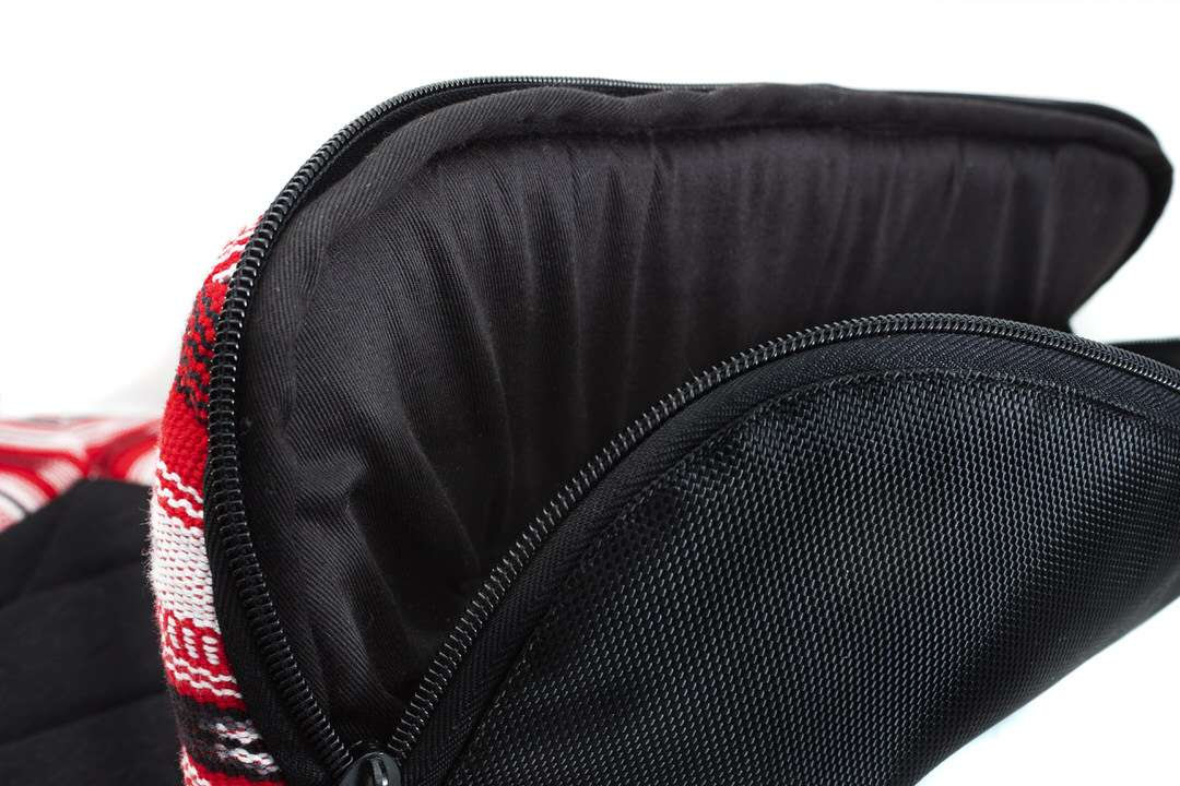 Sleeping bag inside of red and black dog travel bed is unzipped and open like a giant fish mouth