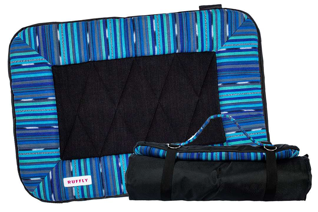 Blue and black dog bed open beside rolled up version with strap