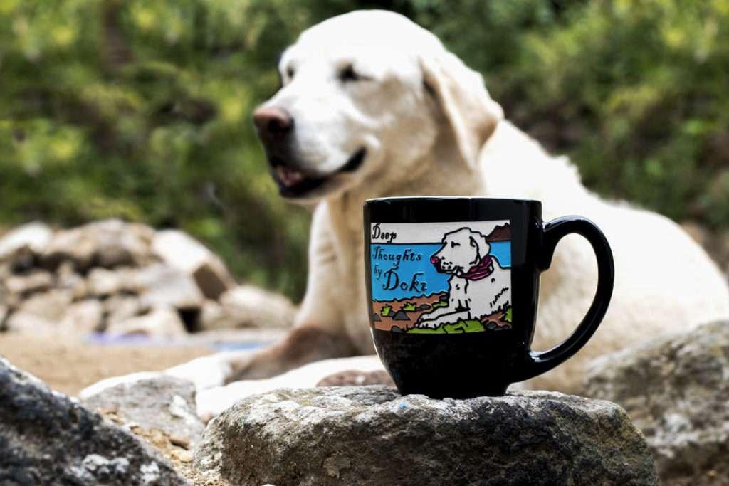 White dog beside black ceramic latte mug with dog artwork engraved and painted