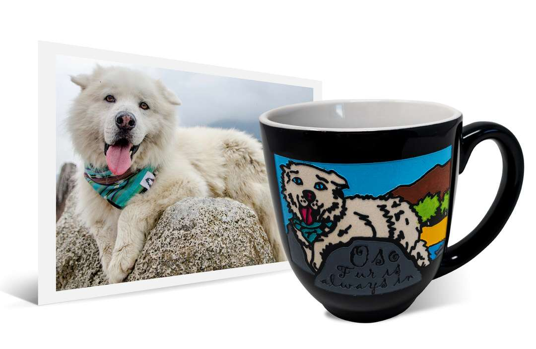 White dog with bandana lays on rock beside same artwork on a ceramic coffee mug