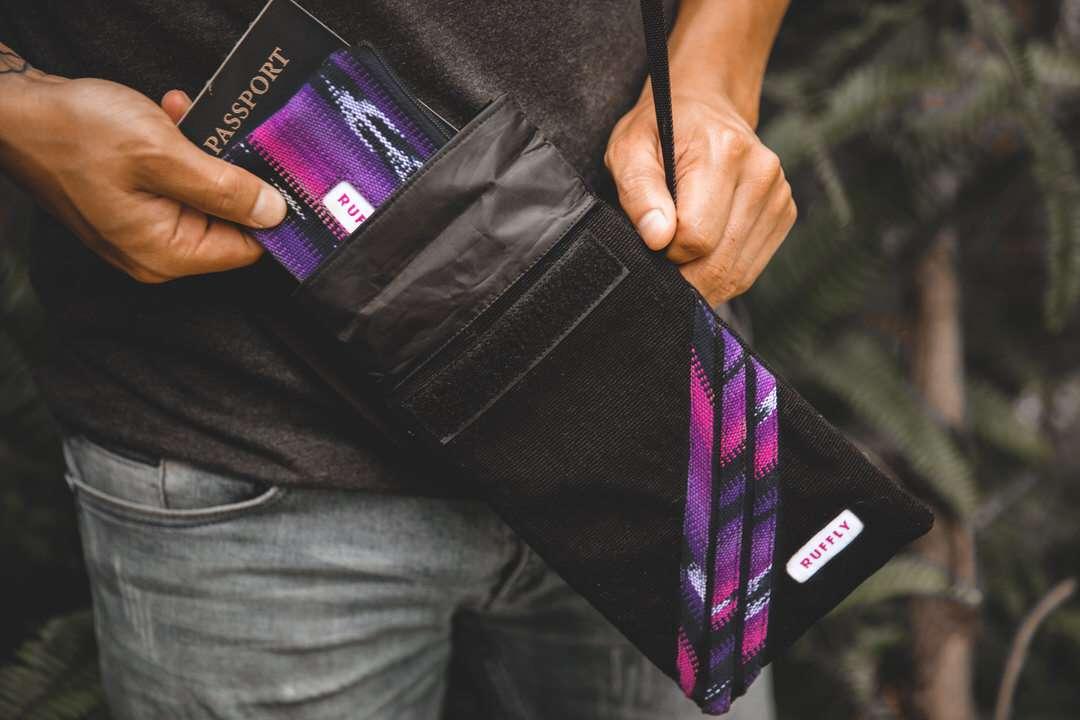 Man places passport and wallet in waterproof crossbody bag