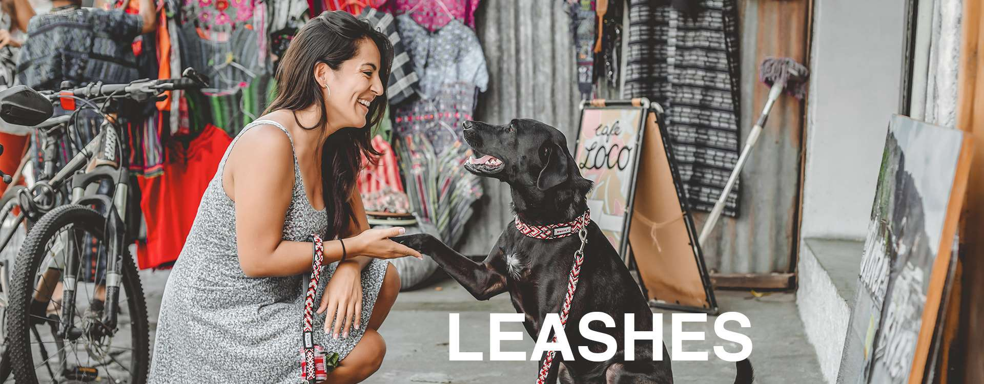"""Woman kneels and holds dog's paw with matching ethically-made outdoor collar and dog leash with overlaid text: """"Leashes"""""""