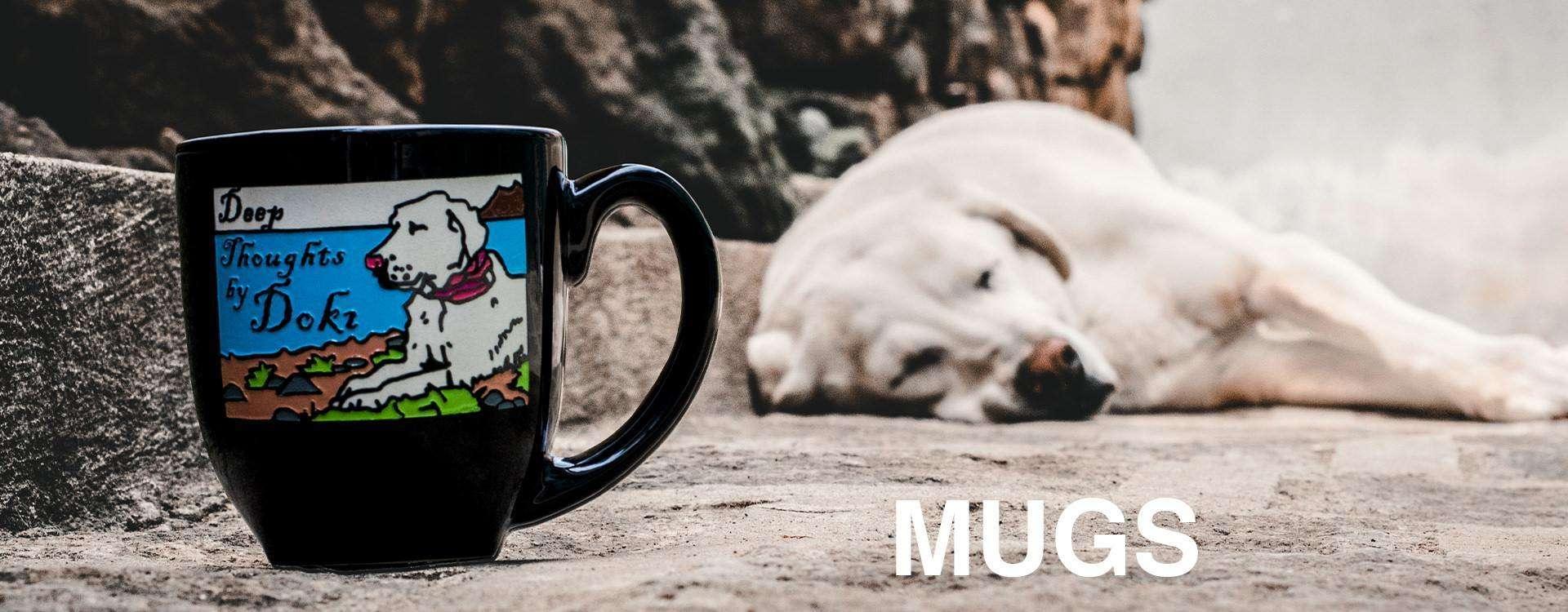 "White dog sleeps on street beside engraved, hand-painted ceramic coffee mug with overlaid text: ""MUGS"""