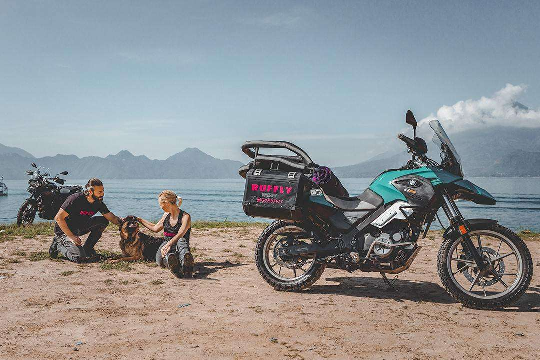 Man, woman, and German shepherd dog share candid moment together beside adventure motorcycles