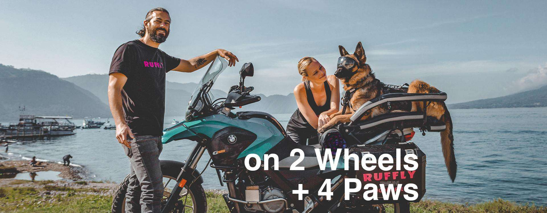 Man, woman, and German Shepherd on adventure motorcycle at turquoise lake with volcanoes