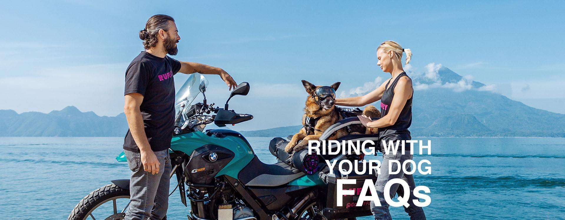 """Man and woman stand beside BMW adventure motorcycle with German Shepherd in motorcycle dog carrier and lake with volcanoes background and overlaid text: """"RIDING WITH YOUR DOG FAQs"""""""
