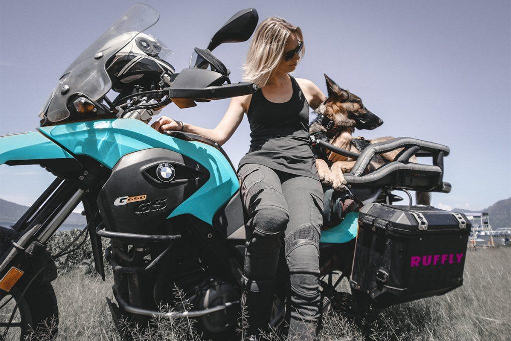 Blonde woman and German Shepherd dog pose together on aqua adventure motorcycle