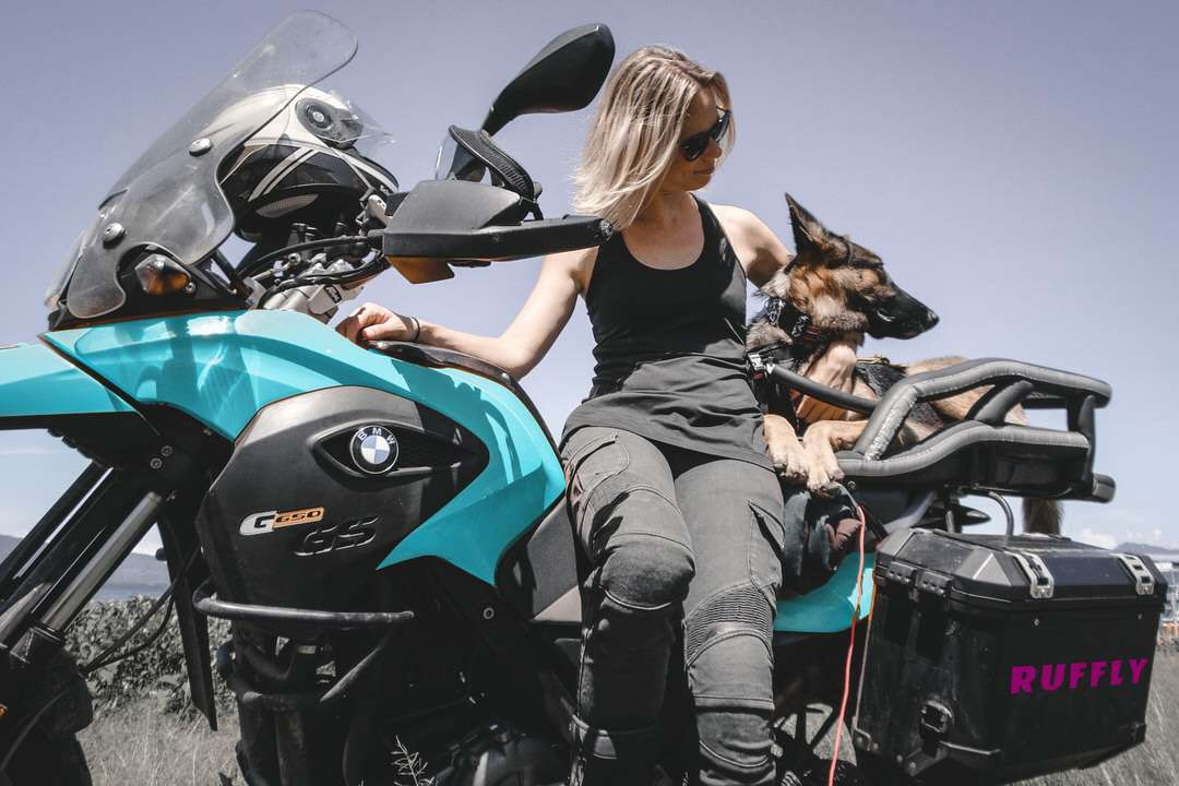 Woman and German Shepherd pose together on adventure motorcycle with motorcycle dog carrier