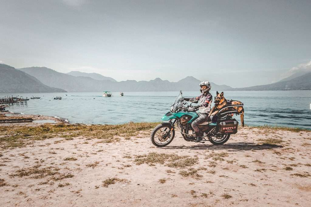Woman rides off-road motorcycle with German Shepherd in motorcycle dog carrier on dirt beside lake with volcanoes