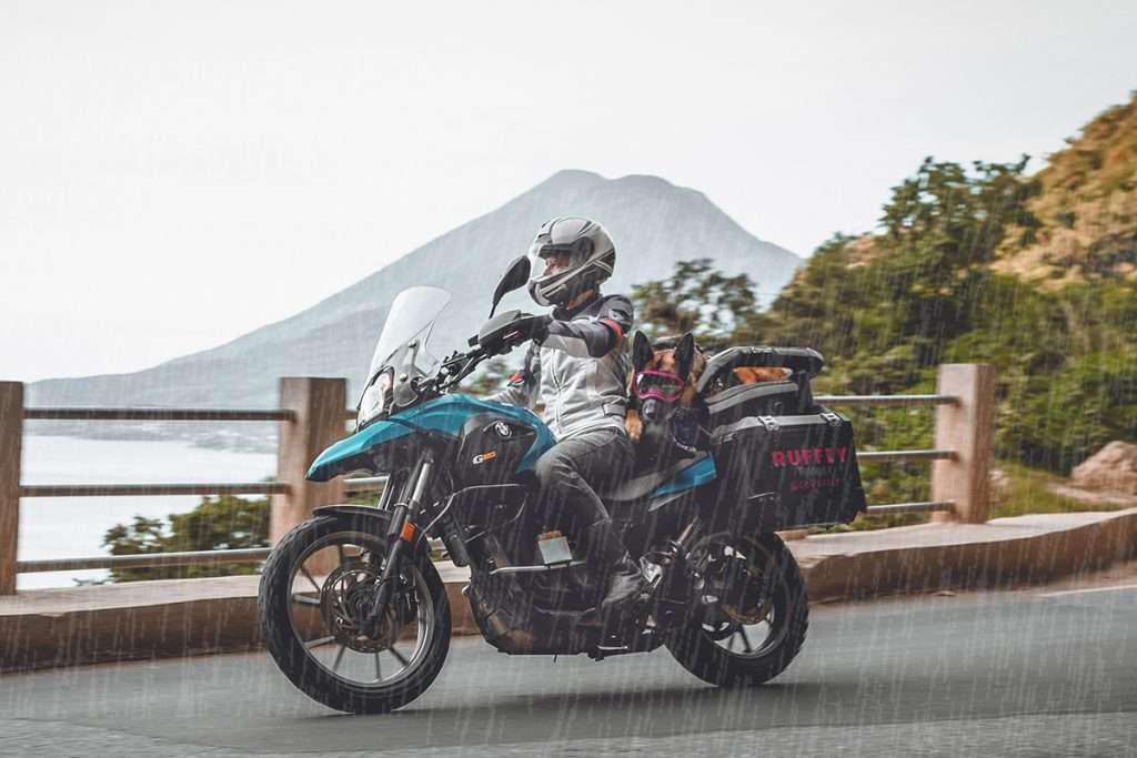 Woman rides adventure motorcycle on twisty mountain road past volcano in the rain with a German shepherd on the back