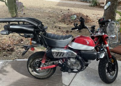 Motorcycle dog carrier mounted to a small Honda motorbike in a driveway