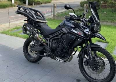 Black Triumph motorcycle in a driveway with a motorcycle dog carrier mounted to the luggage rack