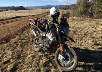 Shaggy brown down lays in a motorcycle dog carrier on a KTM adventure motorcycle beside a dirt road
