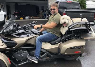 Man on Can-Am Spyder F3-T with Goldendoodle on large motorcycle dog carrier