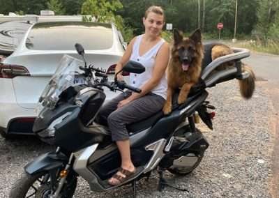 Woman on Honda ADV scooter with a German Shepherd in a large motorcycle dog carrier