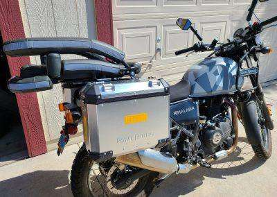 Medium sized motorcycle dog carrier on an Indian-made Royal Enfield stopped beside a garage