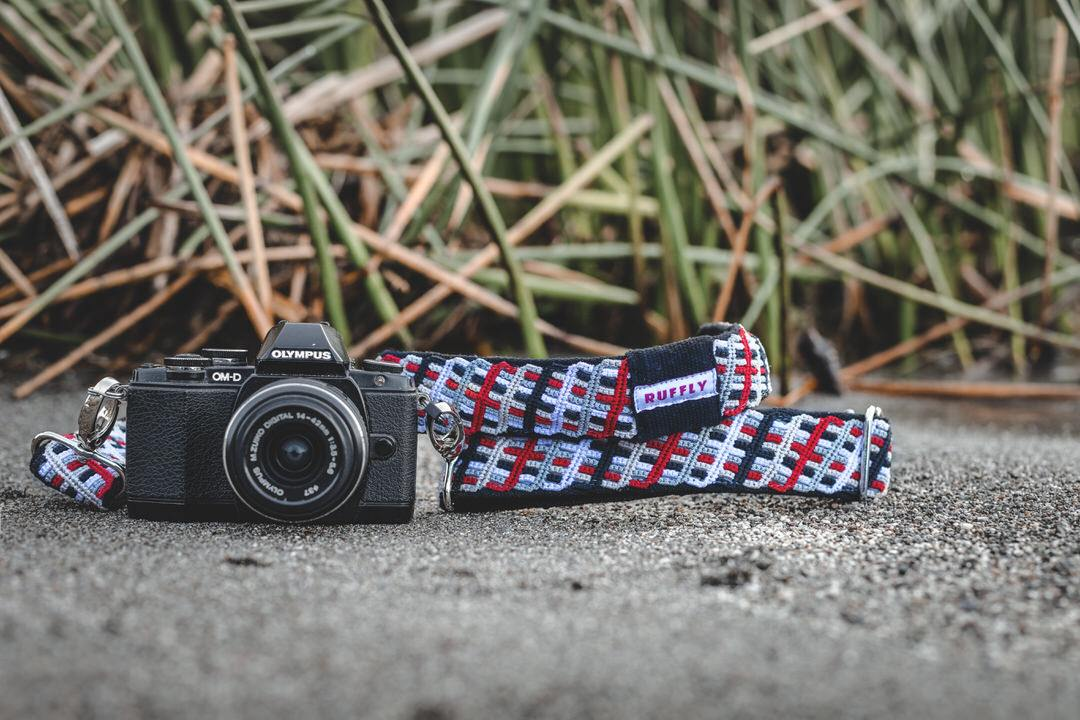 Red. white, and black camera strap with reflective ribbon and naturally dyed cotton on gravel with tall reeds and Olympus camera