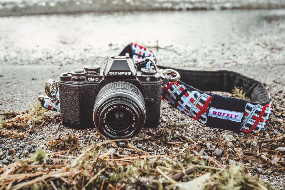Red, white, grey, and black handwoven cotton camera strap with Olympus camera on shore with approaching wave