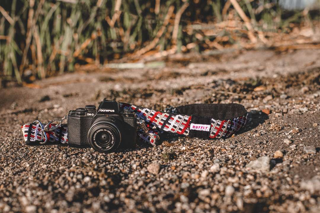 Red and black reflective, artisan-made camera strap with Olympus camera on wet sandy shore