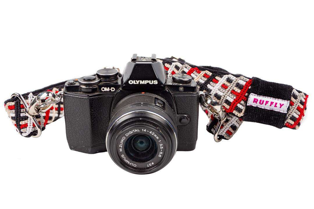 Ethically made camera strap in red and black connected to Olympus camera