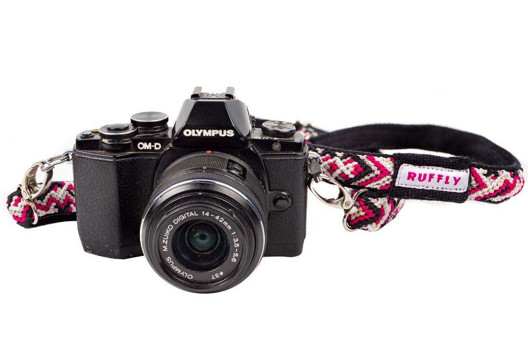 Olympus camera with lightweight sustainable camera strap in pink with reflective ribbon