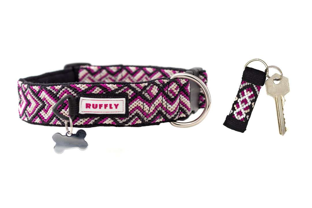 Pink handmade dog collar with metal ID tag beside matching knotted reflective keychain