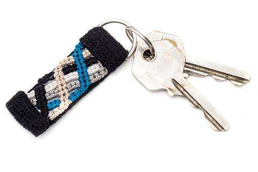 Small blue macrame keychain on black handwoven fabric