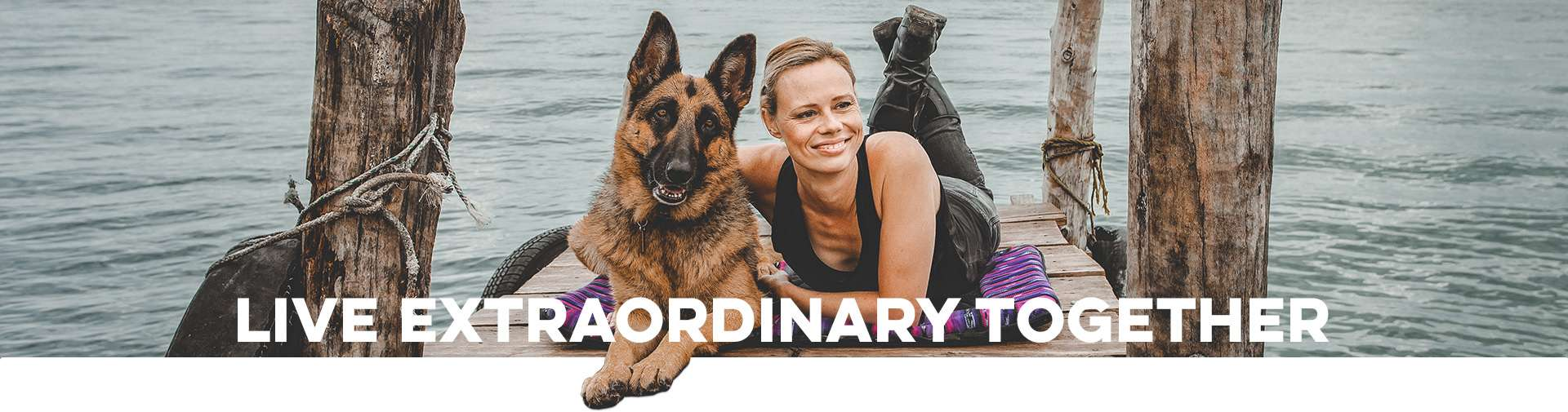 """Young woman and German shepherd dog lay together on dog travel bed on wooden dock with overlaid text: """"LIVE EXTRAORDINARY TOGETHER"""""""