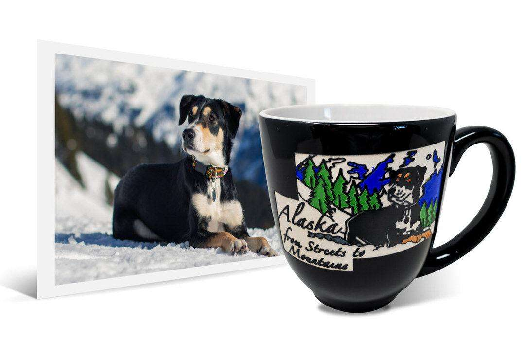 "Original photo of black and white dog beside custom black coffee cup that says ""Alaska, from Streets to Mountains"""