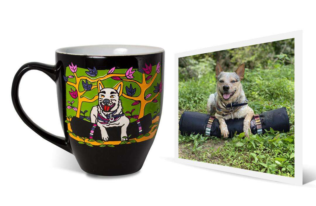 Photo of grey dog sitting over rolled-up travel bed among grass next to mug with same personalized artwork on it
