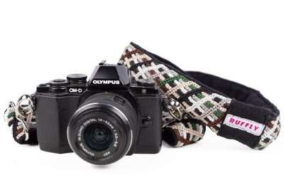 Brown and green handwoven camera strap with naturally dyed cotton and built-in cushion attached to Olympus camera