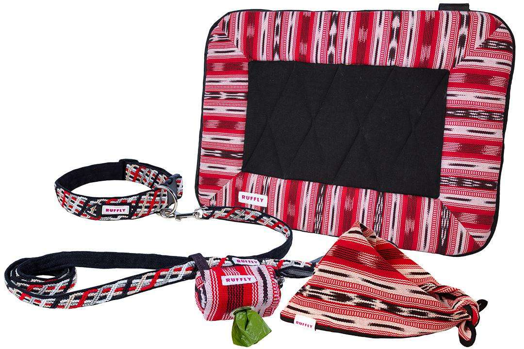 Outdoor dog kit in red and black that includes collar, leash, bed, bandana, and poop bag holder