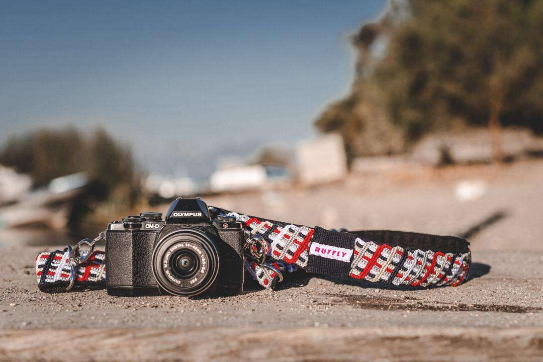 Reflective outdoor camera strap in red and black with Olympus camera on sand