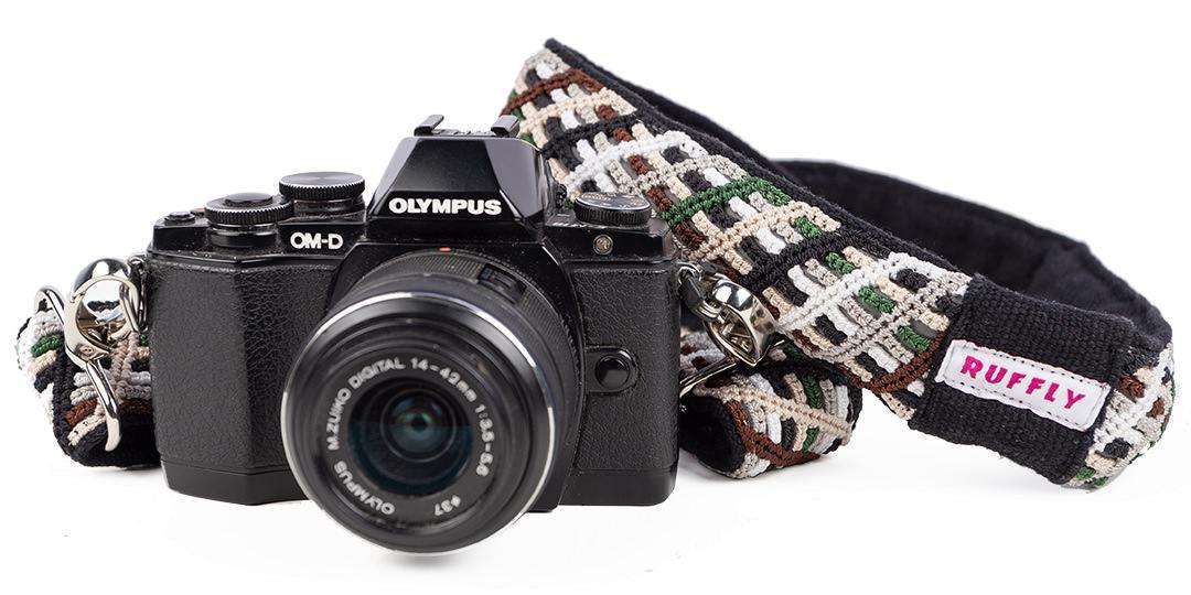 Brown, green, and black reflective strap connected to Olympus Camara with white background