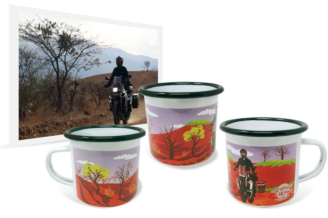 Photo of man riding adventure motorcycle in desert beside personalized enamel travel mug with wraparound artwork