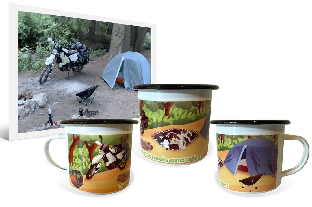 Photo of motorcycle and tent at campsite beside personalized artwork on enamel travel mugs
