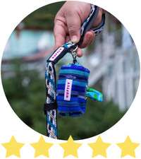 Hand holds blue dog leash with matching poop bag holder and plastic bag