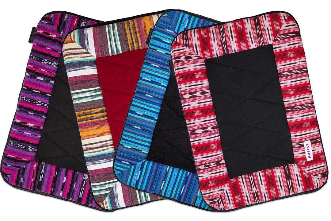 Dog travel bedrolls arranged in four unique and distinctive handwoven colors and designs