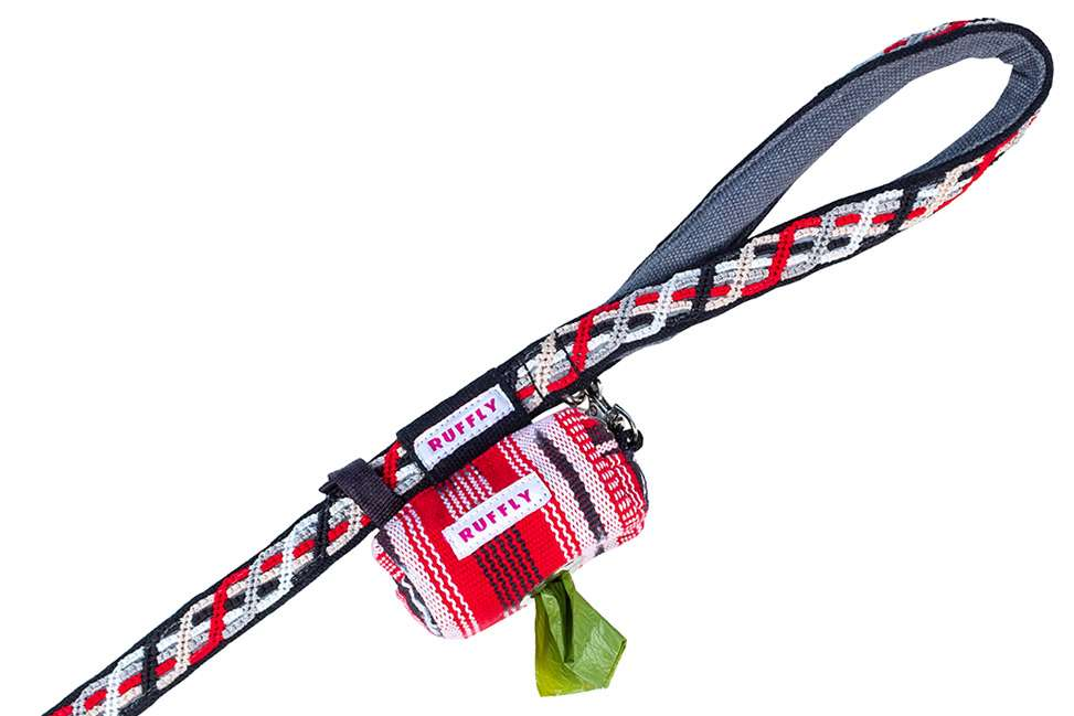 Closeup of red reflective outdoor dog collar handle with handwoven poop bag holder connected to the stainless D-ring