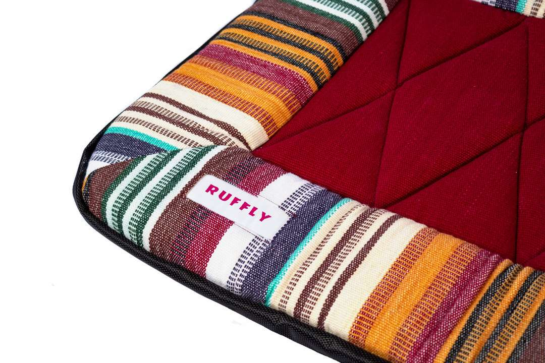 Closeup of handwoven top of dog travel bed with embroidered inlaid label and natural colors design